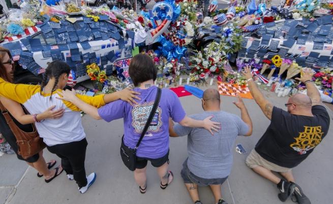 Хора отдават почит на загиналите полицаи пред мемориала пред полицията в Далас