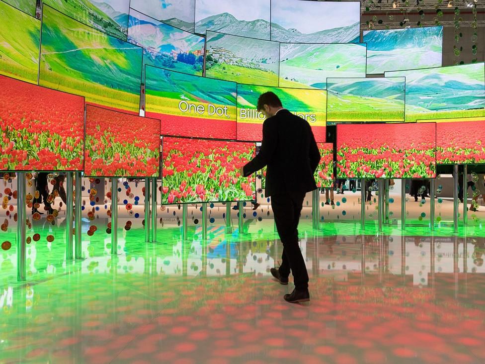 - Човек стои пред телевизионни екрани работещи на базата на технологията на квантовите точки, ден преди началото на IFA 2016 международния панаир за...