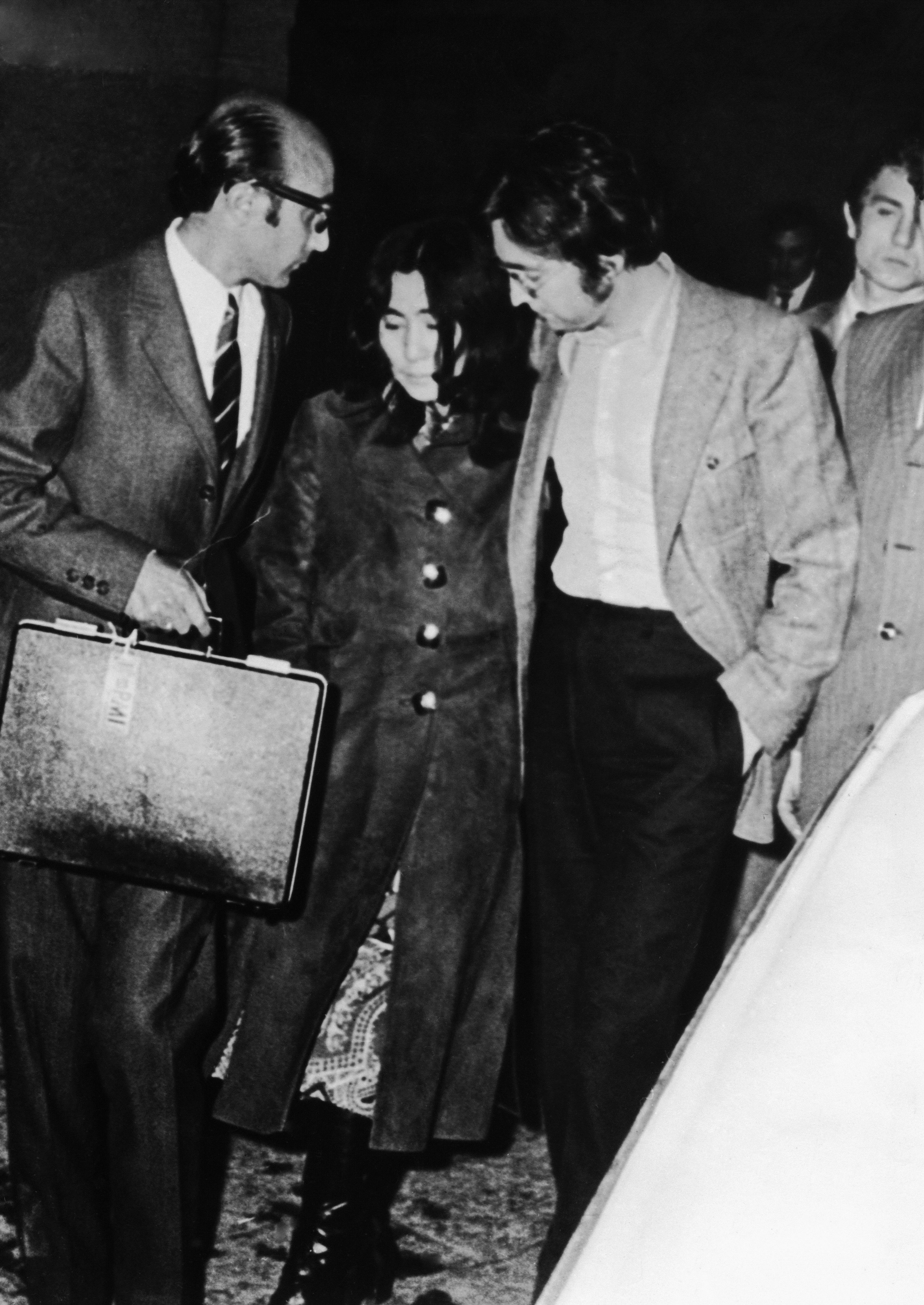 <p>Джон Ленън успокоява съпругата си Йоко Оно, докато напускат полицейски участък в Майорка, където са разпитани за отвличането на дъщерята на Оно - Киоко. Бащата на 7-годишното момиченце обвинява оно в отвличане, но тя отрича твърденията, че той имал пълно попечителство над детето. (26 април 1971 г.)</p>