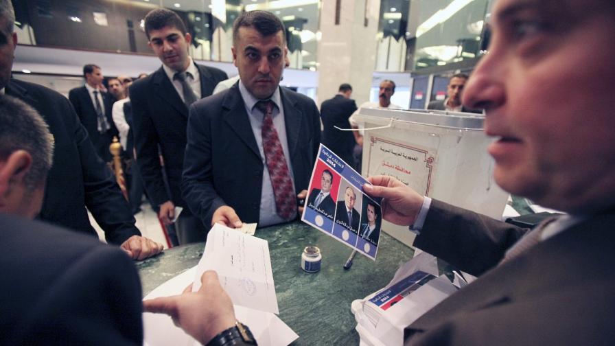 Член на избирателна секция в Дамаск държи бюлетина с тримата кандидати