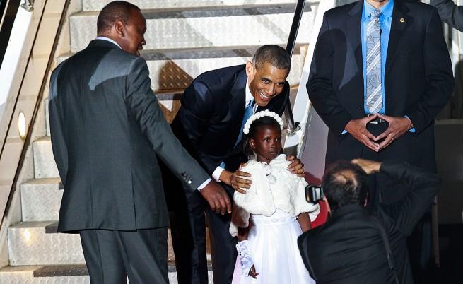 Барак Обама позира с момиченце при кацането си на летището в Найроби