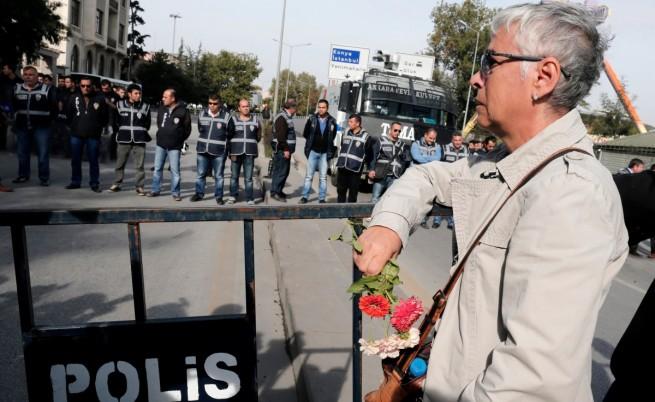 Жена с цветя в ръце пред полицейските заграждения на мястото на атентатите в Анкара