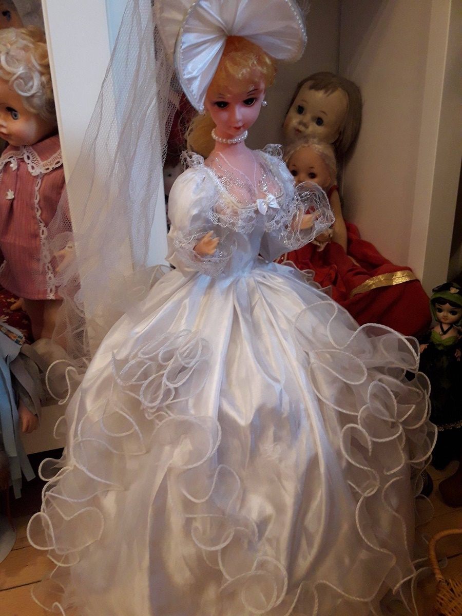 """Пеещата булка на Ванга.<br /> Красива, облечена в бяло, привела замислено глава.<br /> Куклата е подарък на музея от фондация """"Ванга"""", заедно с още няколко кукли."""