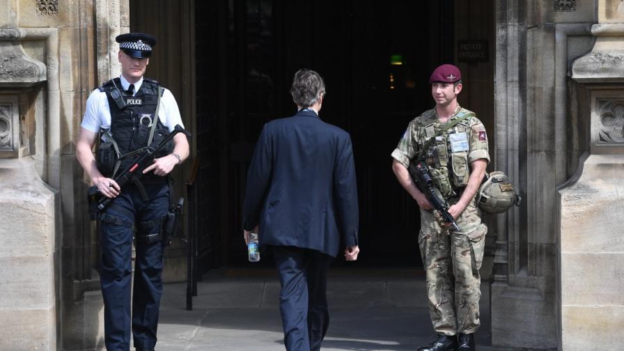 Полицай и войник на пост пред сградата на парламента в Лондон