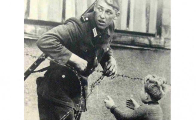 Войник от ГДР прекарва малко момченце през Берлинската стена