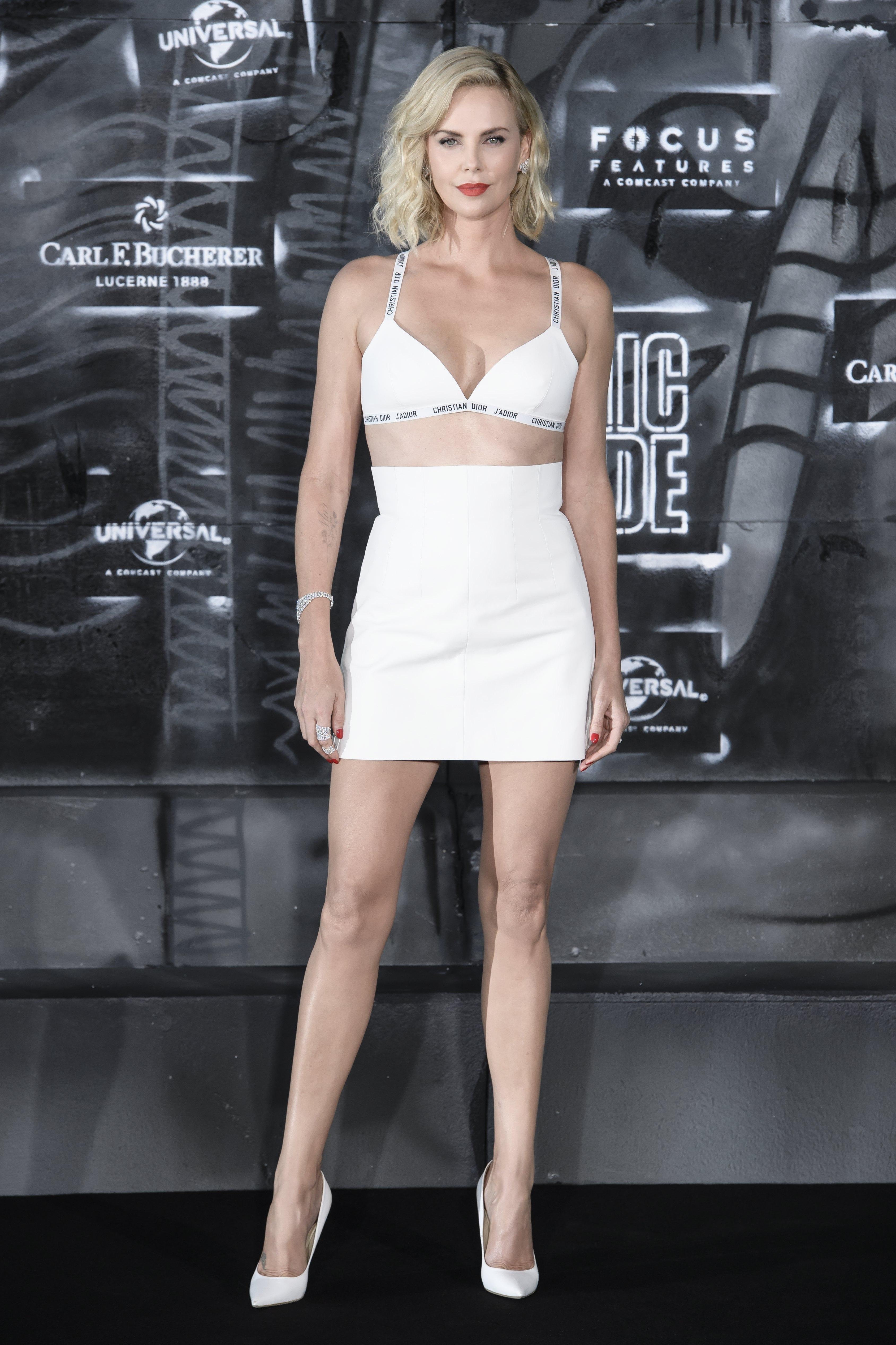 """Само преди 2 дни се проведе премиерата на екшън филма """"Атомната блондинка"""", но днес кино критиците не коментират лентата, а появата на холивудската звезда Чарлийз Терон на червения килим. 41-годишната актриса се появи по къса бяла пола и сутиен, брандиран с """"Диор"""" и обра овациите с перфектното си тяло и смелостта."""