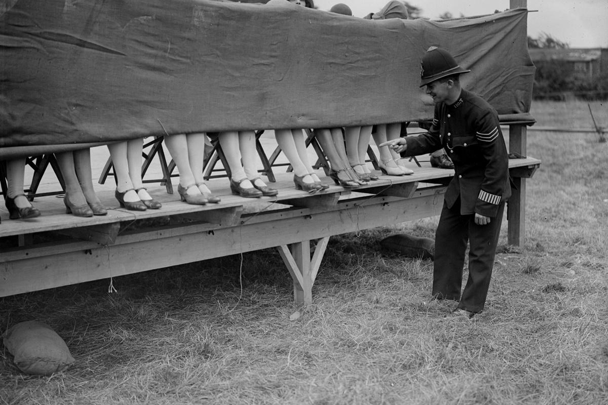 10 юли 1930 г.: Полицай оценява глезените на участнички в конкурс за най-хубави глезени в Лондон, Англия.