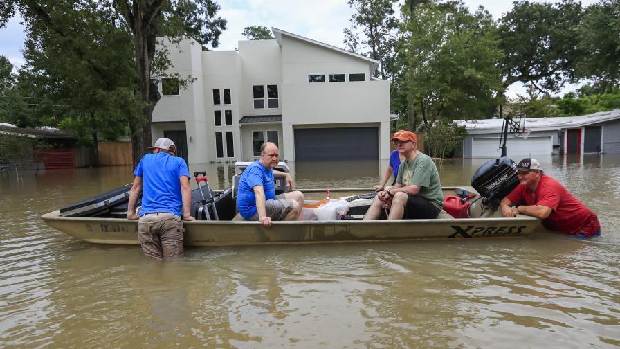 """Пострадали от бурята """"Харви"""" се придвижват в лодка между наводнените си къщи"""