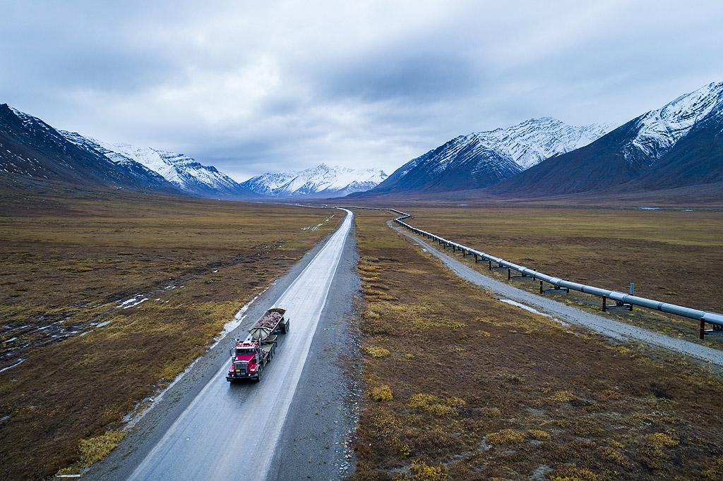 Гигантски камиони за доставки изстрелват големи облаци прах и скали, докато се движат между Феърбанкс и нефтените полета на Северния склон.