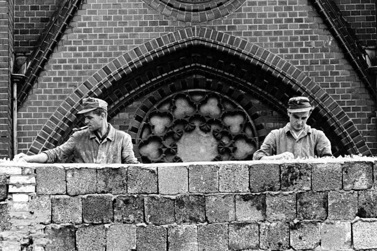 Военни поставят начупени стъкла по стената, за да затруднят прескачането ѝ.