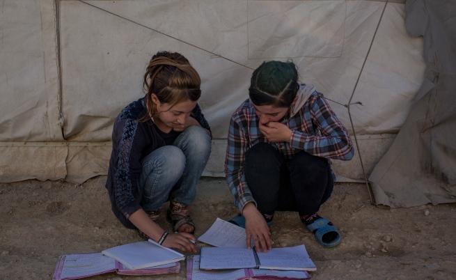 Язидски момичета подготвят домашните си в бежански лагер край Мосул.