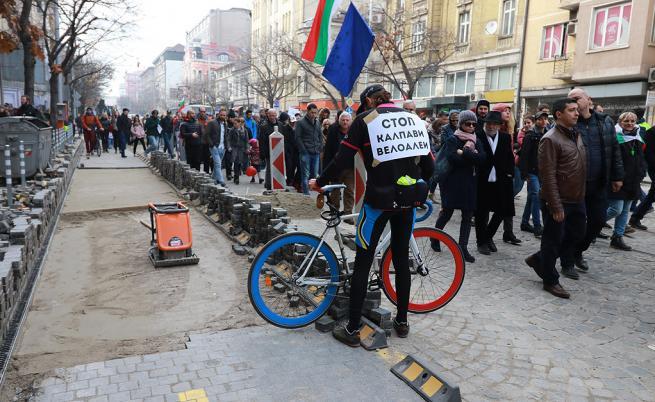 """Недоволни софиянци излязоха на протест срещу столичния кмет Йорданка Фандъкова, организиран от НПО """"Спаси София"""". Протестът е под надслов Данче, слез  протест за цялостно творчество"""". Основните причини за недоволството са презастрояването в столицата, мръсният въздух и компрометирането на редица пътни участъци, неизползваеми велоалеи, унищожаване на паметници на архитектурата, бавен градски транспорт."""