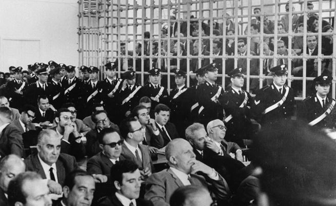 Октомври 1967 г., Италия: съдебен процес срещу членове на мафията. Те са поставени в голяма килия, защото съдебната зала се оказва твърде малка, за да ги задържи.