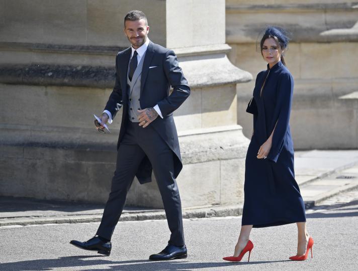 <p>Дейвид и Виктория сияят в своите официални визии, подбрани специално за сватбата на годината. Дейвид е с костюм, а Виктория с черна рокля и червени токчета, съчетани с черна шапка.</p>