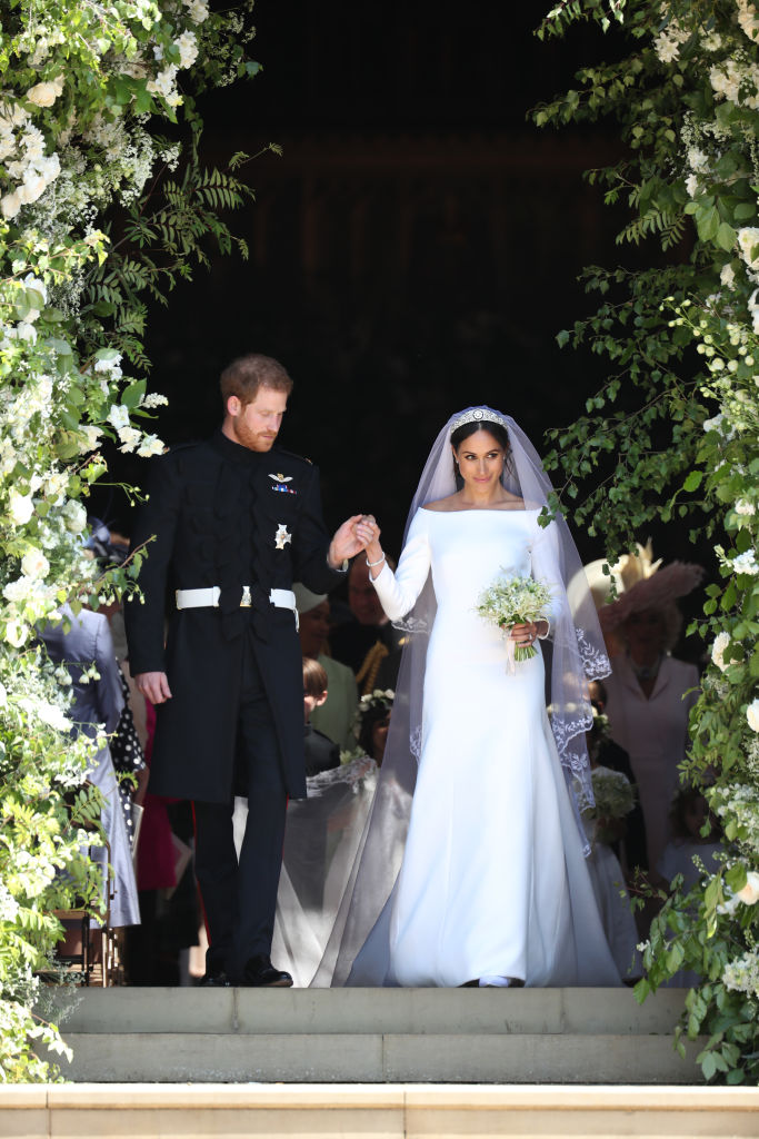 """Американската актриса Меган Маркъл изненада мнозина, след като избра Клеър Уейт Келър, британската дизайнерка, работеща за френската модна къща """"Givenchy"""", да сътвори роклята ѝ за сватбената церемония. Меган бе ослепителна, а принц Хари не успя да сдържи сълзите си от вълнение. Роклята бе с ръкави, покриващи 3/4 от ръцете, и почти открити рамене, изчистен дизайн и 5-метров шлейф с копринен тюл, бродиран с цветя от държавите, членуващи в Общността на нациите. Всяко от растенията е типично за отделните 53 страни от организацията."""