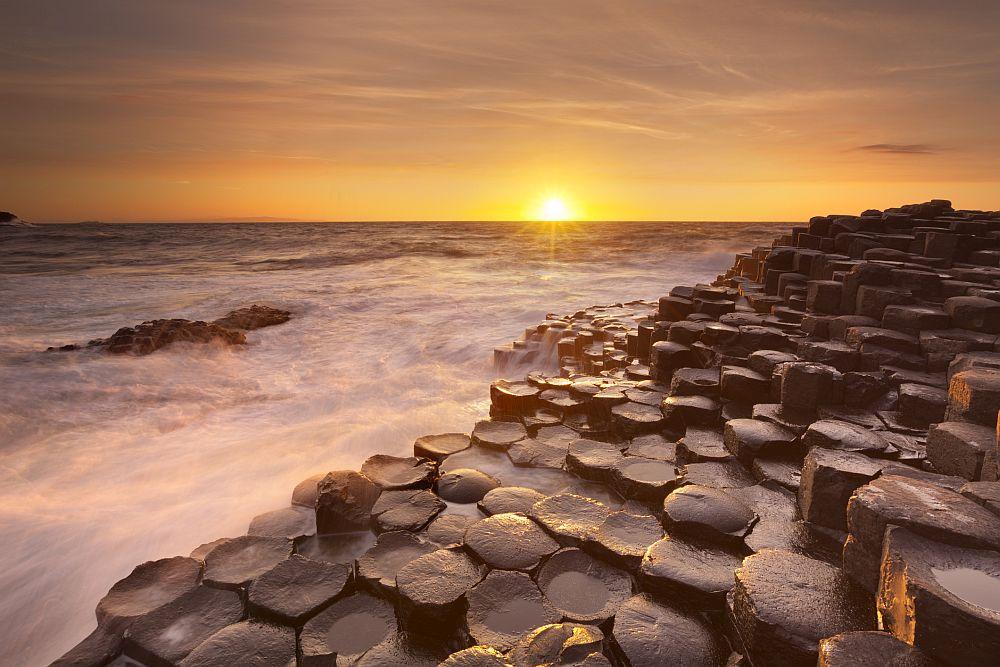 <strong>Пътят на великаните, Ирландия </strong><br> <br> По крайбрежието на Северна Ирландия се спускат повече от 38 000 базалтови колони, които като огромна магистрала-трамплин изчезват в морето. Вулканичните изригвания са оставили след себе си перфектно оформени шестоъгълници, групирани в клъстъри като пчелна пита. Това е т.нар. Път на великаните - едно същинско природно чудо.