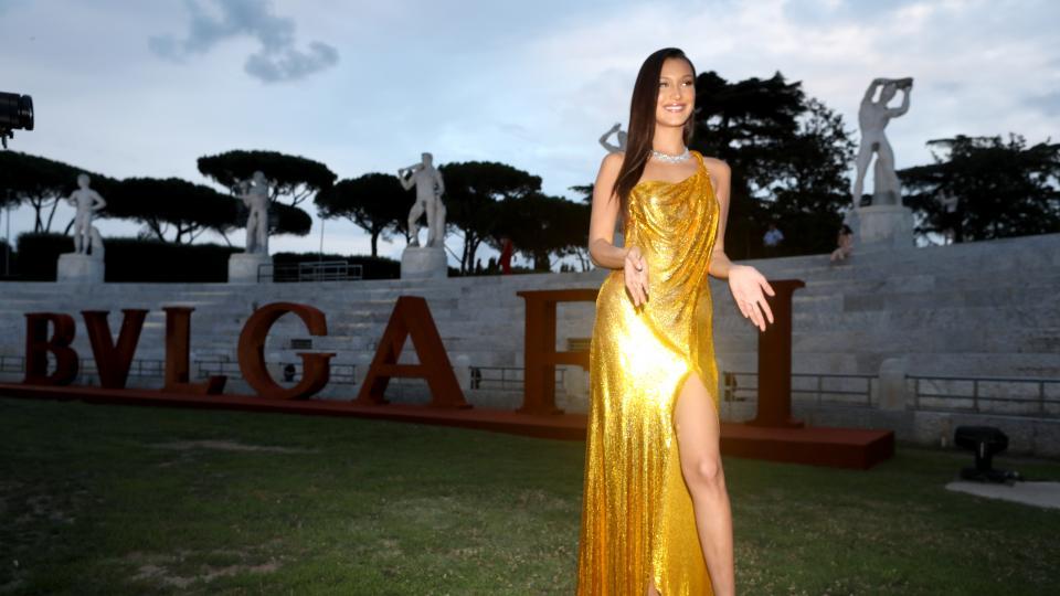 Световноизвестният моделБела Хадид за пореден път показа, че сияе като истинско бижуна червения килим. Красавицата бе сред гостите на светско събитие в Италия и привлече всички погледи с изумителна рокля със златисти отблясъци.  Акцент в тоалета бе голямата цепка, която разкривашебезупречните крака на модела. Бела Хадид бе подбрала сребристи бижута като допълнение към роклята.