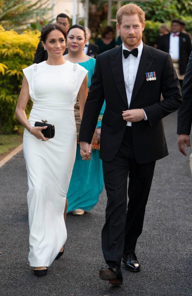 За приема с кралицата и краля на Тонга Меган бе избрала красива бяла рокля Theia с камъчета на раменете. Цената на роклята е 1,290 долара