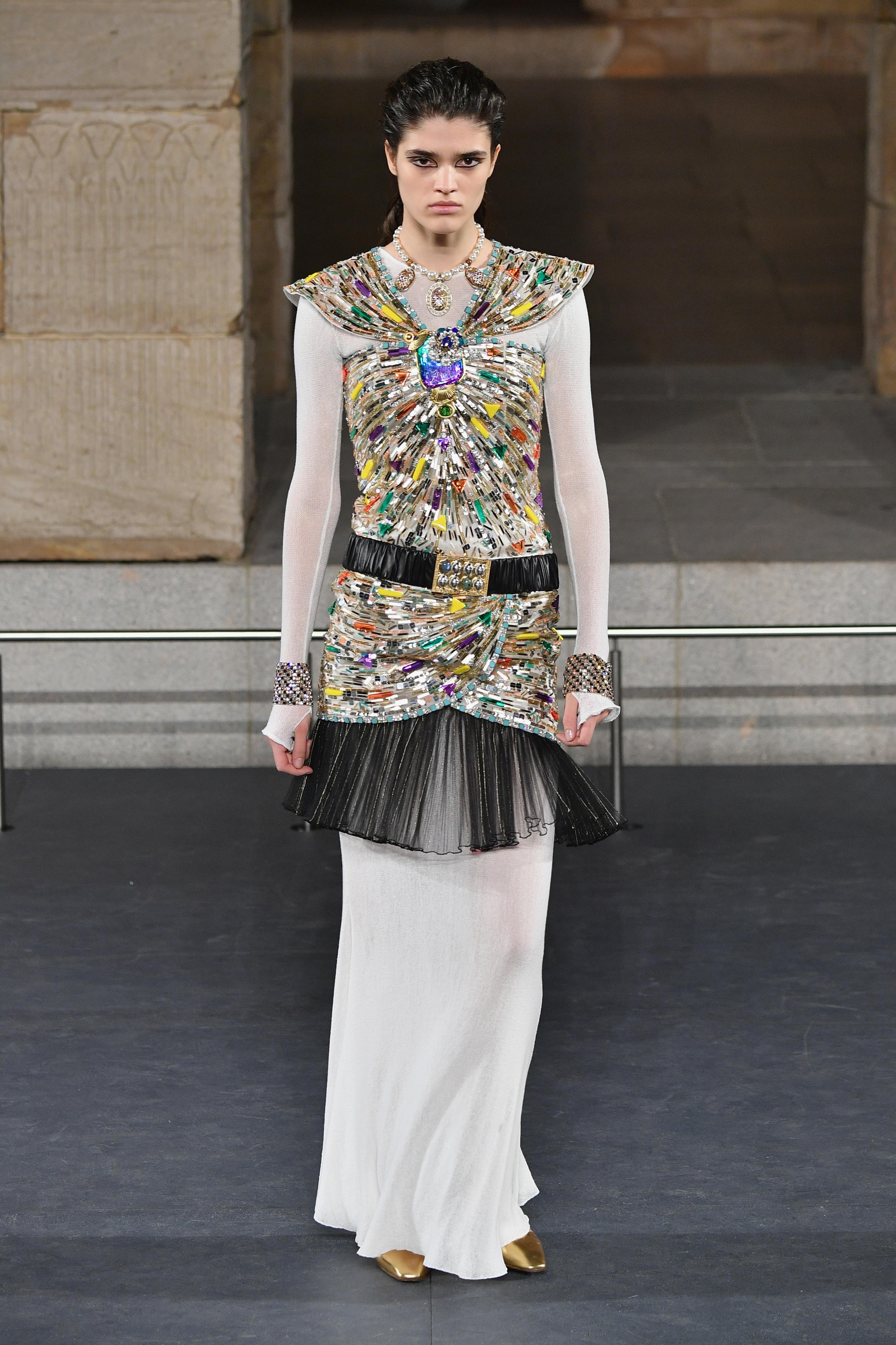 """Малко преди ревюто в Ню Йорк се появиха постери, изобразяващи манекенка с култовия тайор, станал символ на """"Шанел"""", носеща корона и факел, наподобяващи тези на Статуята на свободата. Но главният акцент на артистичния директор на модната къща Карл Лагерфелд все пак падна върху неговата """"холивудска визия"""" за Древния Египет. Тя бе вдъхновена от филма """"Клеопатра"""" на Джоузеф Манкиевич от 1963 година с участието на Елизабет Тейлър."""
