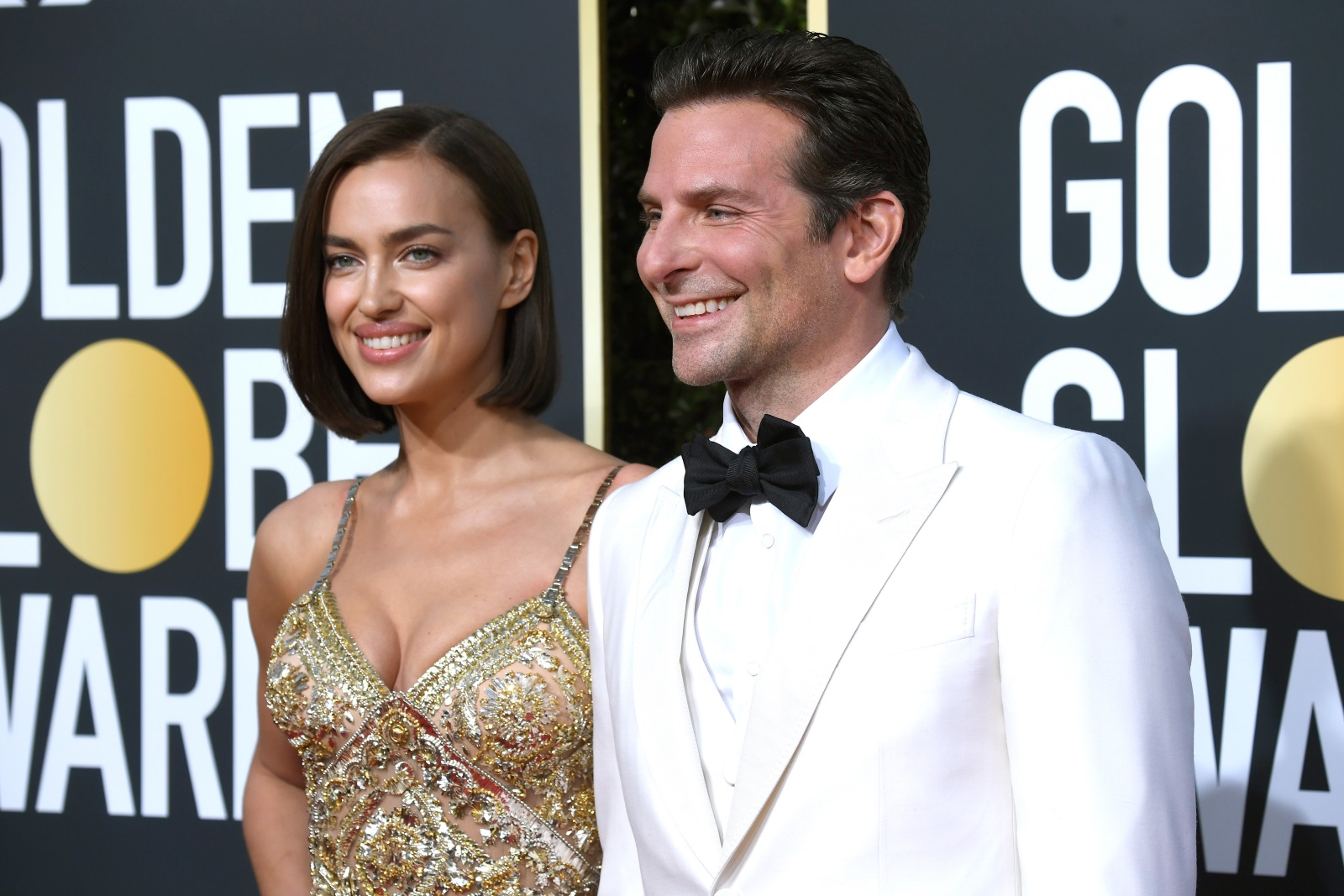 """33-годишната Ирина Шейк изглеждаше зашеметяващо с прозрачна рокля със златни и сребристи елементи и висока цепка от лявата страна. Моделът показа и новата си прическа тип """"боб"""". Брадли Купър, който имаше две номинации за филма си A Star Is Born, бе избрал за повода смокинг в бяло."""