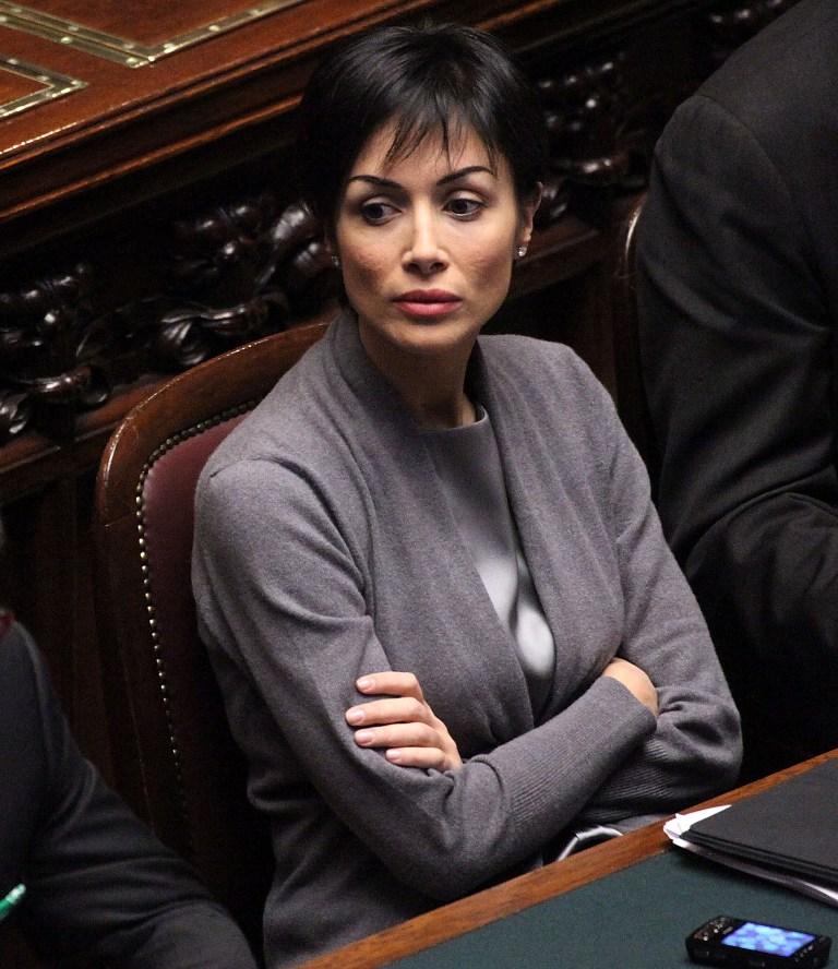 """Мара Карфаня – италиански политик, бивша манекента и бивша телевизионна водеща. Политическата й кариера започва през 2004 г., когато става член на партия """"Форца Италия"""". Тя превръща борбата за правата на жените в своя основна кауза."""