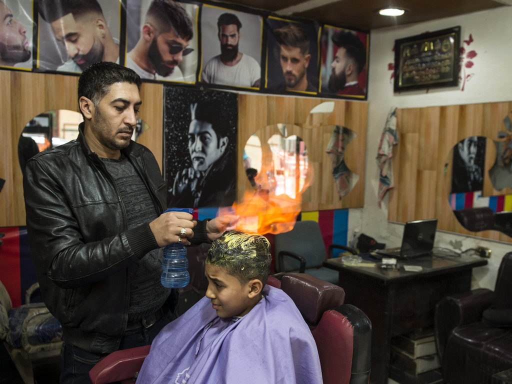 Египетският бръснар Хамада Рамадан използва огъня, за да изправи косите на клиентите си, в бръснарския си салон разположен в квартал Файсал, Гиза, Египет.