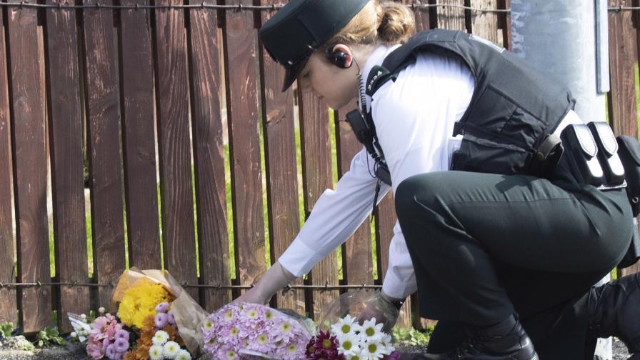 Полицай поставя цветя на мястото, където беше застреляна журналистка