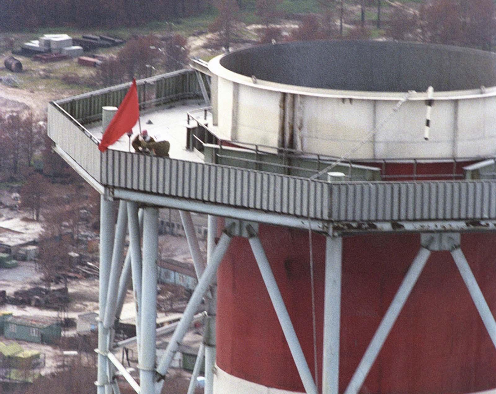 По заповед на съветските власти трима мъже се изкачват на 78 метра висосчина по стълбите на реактор номер три, за да поставят червен флаг, показващ, че разчистването на реактора е приключено.