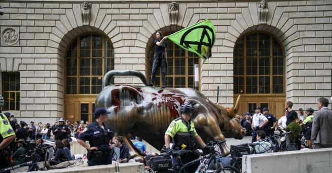 Протестиращи екоактивисти заляха с червена боя прочутата статуя на бик