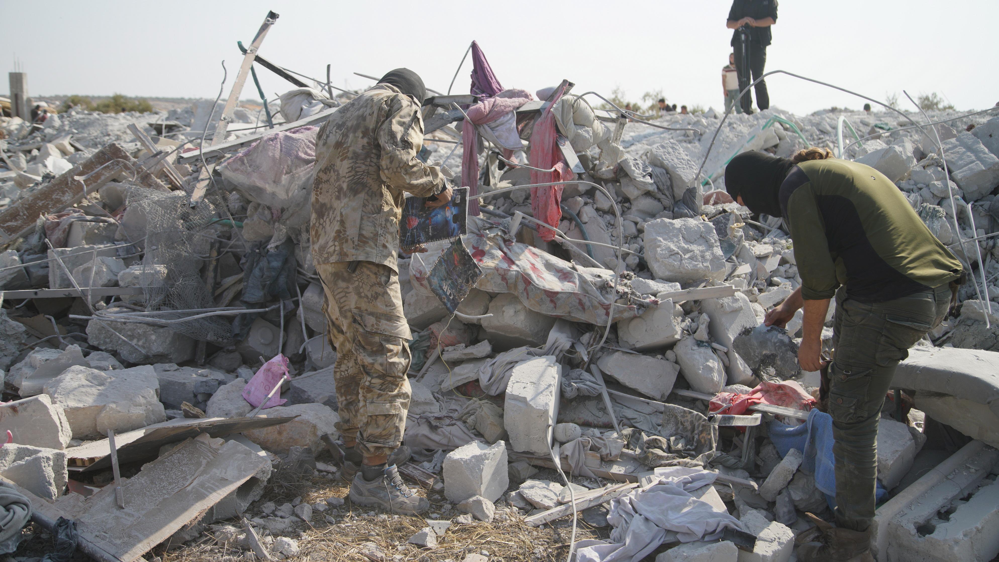 """На снимките: Хора обикалят около развалините на разрушените сгради на мястото, което беше обстреляно в неделя. Според съобщения загинали са девет души, включително Абу Бейкър Ал Багдади - лидерът на """"Ислямска държава"""". Кадрите са заснети близо до село Бариша, провинция Идлиб, Сирия, 27 октомври 2019 г. (издаден на 28 октомври 2019 г.)"""