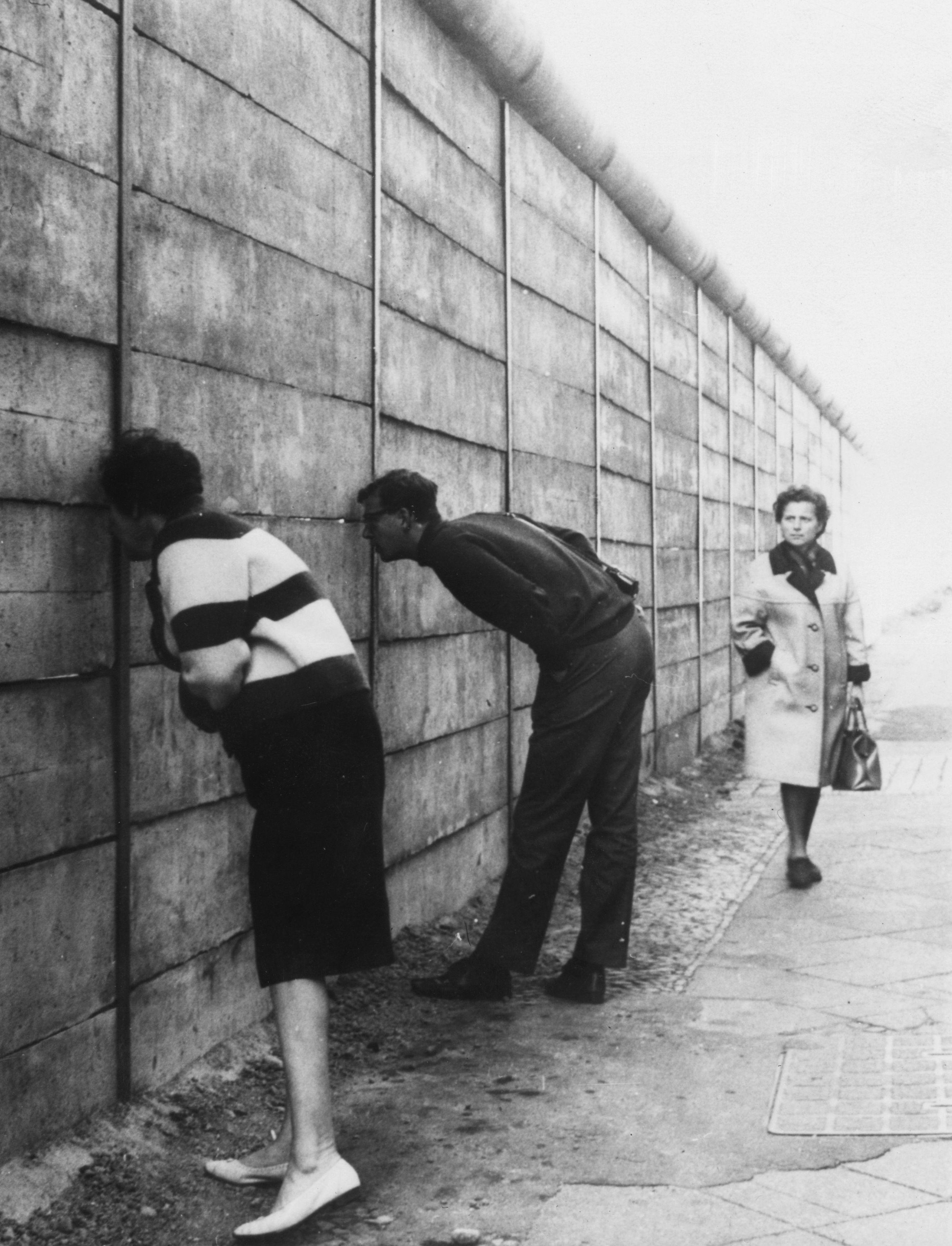 <p>Хора от Западен Берлин надничат през пролуки в Стената, за да видят какво се случва от другата страна.&nbsp;</p>