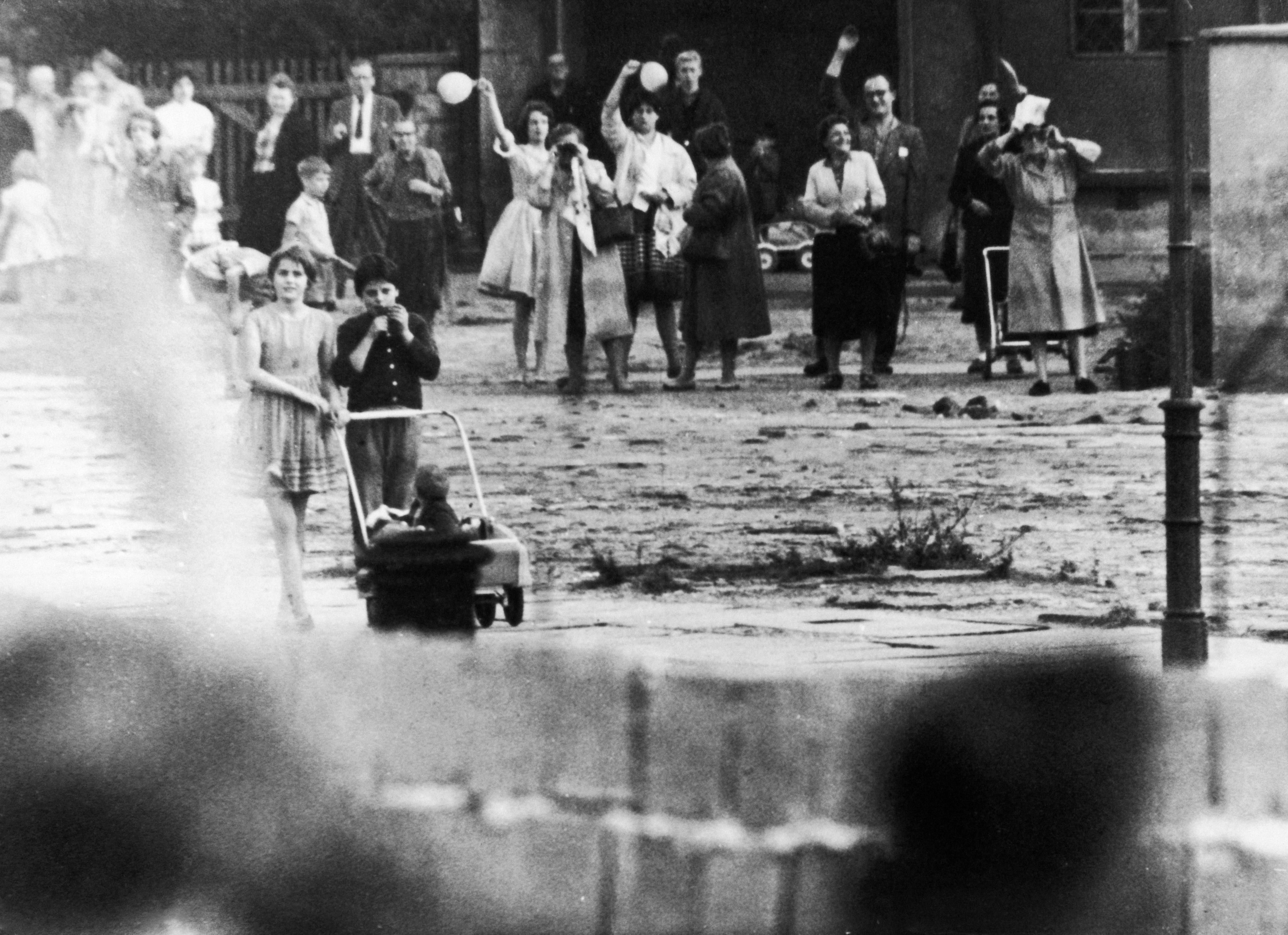 <p>Семейства и приятели, някога съседи, сега стоят разделени и махат един на друг над Берлинската стена.</p>