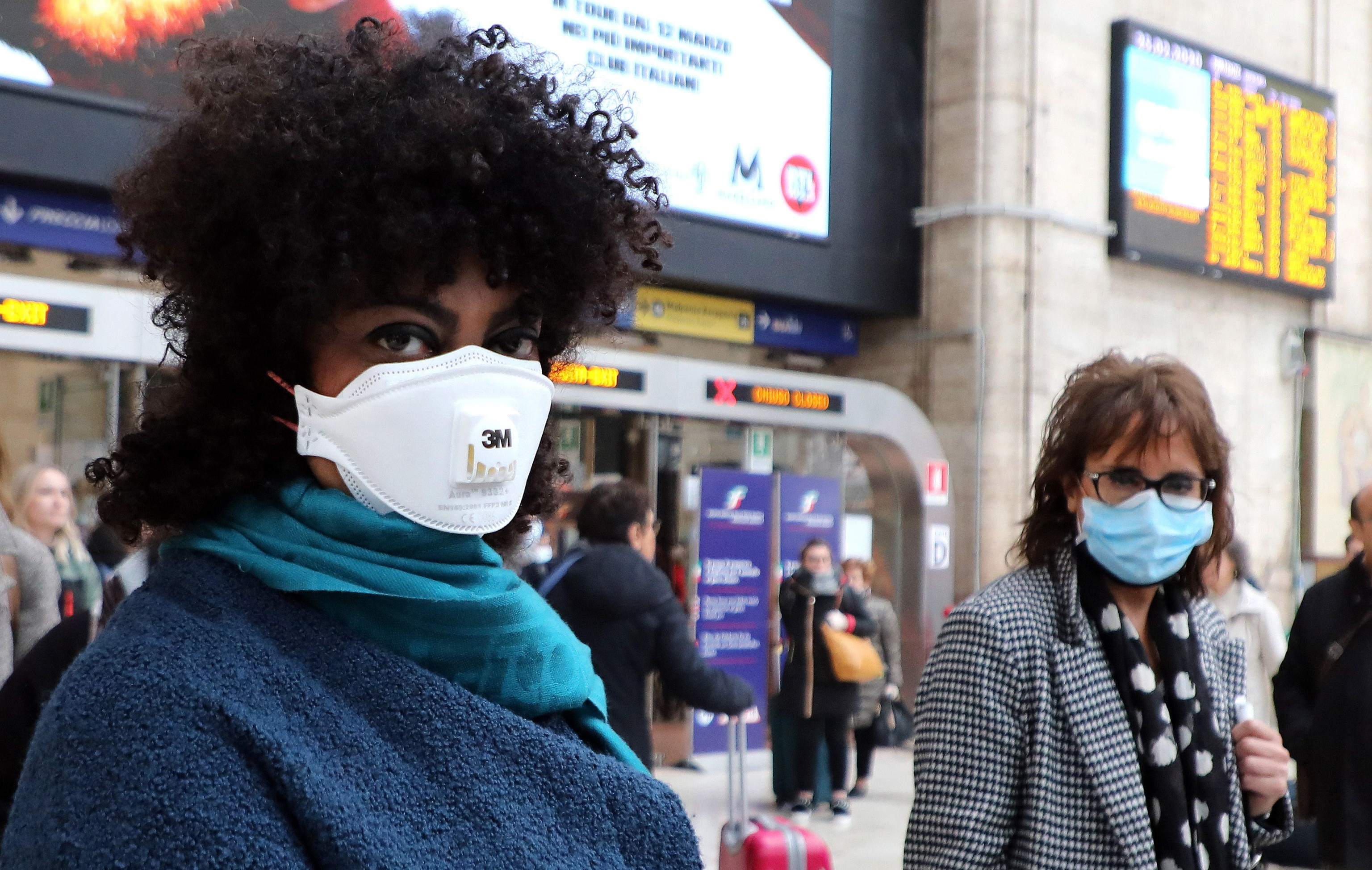 <p>Пътуващите също носят защитни маски за лице, Централна гара, Милано, Италия</p>