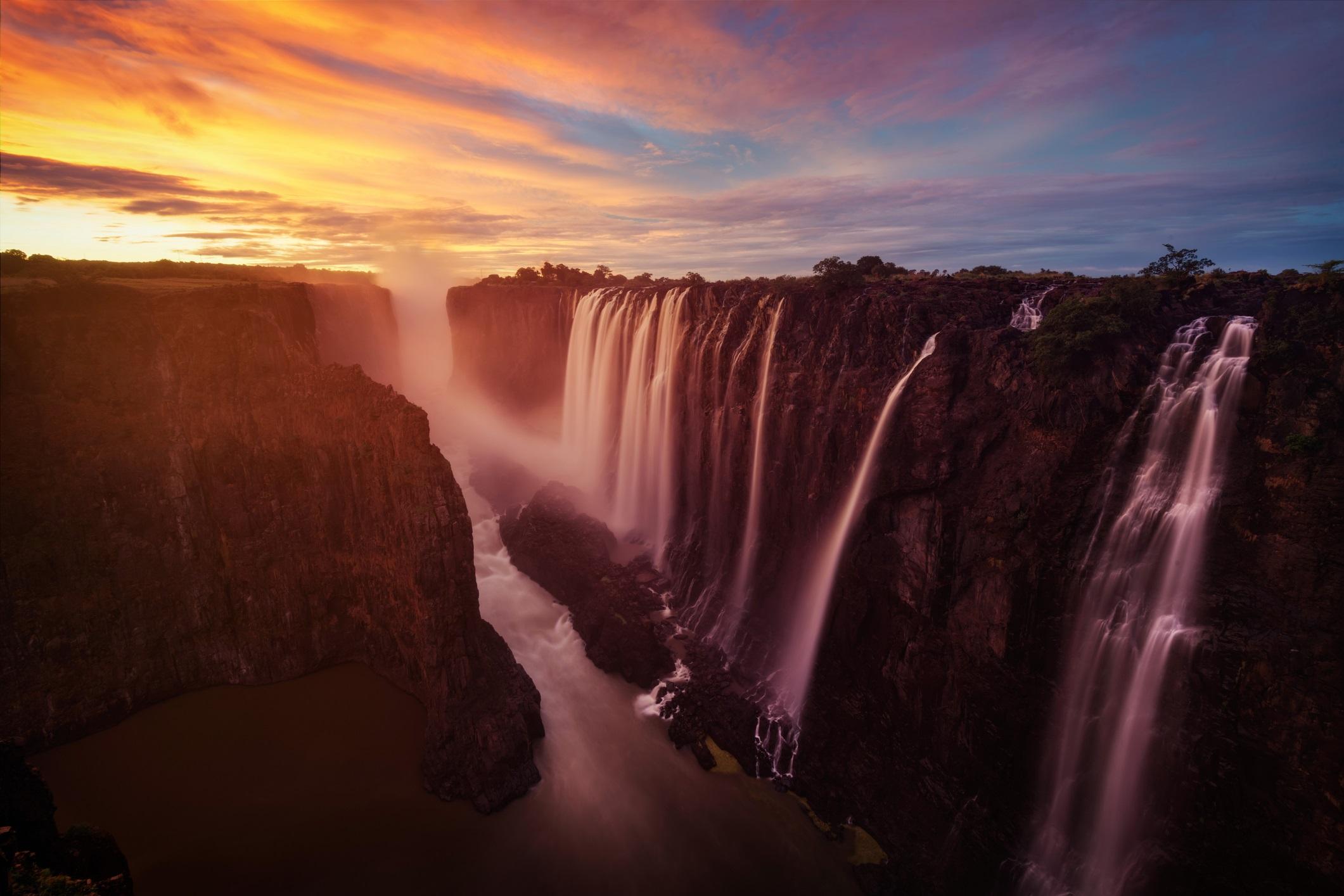 <p><strong>Виктория, Замбия и Зимбабве</strong></p>  <p>Групата водопади Виктория, включени в списъка на ЮНЕСКО със световното културно и природно наследство, се намира на река Замбези между африканските държави Замбия и Зимбабве. На това място водите падат от височина 100 метра и образуват водна стена с дължина 1708 метра, което прави Виктория в най-широкия водопад в света.</p>