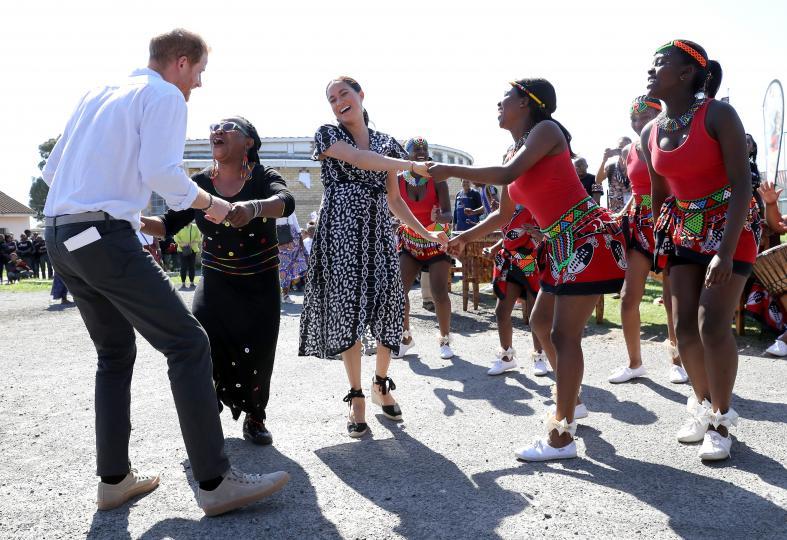 <p>По време на посещението си в Африка през 2019 г.&nbsp;принц Хари и Меган Маркъл са увлечени в танц от местните жители.</p>