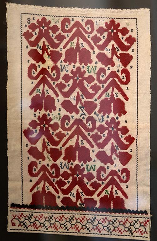 <p>Свиленица от Лопушна. В книгата на Любен Маслинков този ръкав е отпечатан в обратна посока. Той определя фигурките като лалета, а ние, подпомогнати от подладжицата, виждаме цяло стадо от рогати същества. В горната дясна част е извезана цифрата три, а власити са извезали латински букви &ldquo;W&rdquo; &ldquo;N&rdquo; &ldquo;Z&rdquo;. Празните полета са осеяни с малки черни кръстчета и стрелички. Ръкавът, везан около 1900 година, крие много неразгадани послани. Бордюрът е зигзаг. Подладжицата е нежна черно-червена лозница, обградена със зигзаг, може би симбвол за вода. Тази свиленица е емблема на нашата семпла и свидна изложба &bdquo;Шевици от историята на Женски пазар&rdquo;.</p>