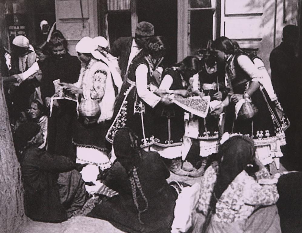 <p>Снимка на група жени на пазар в София около 1910-1915 г., разглеждащи свиленици за продажба.</p>