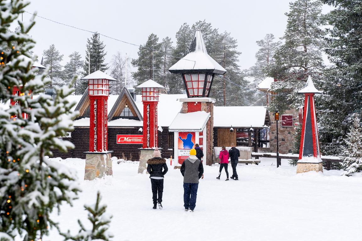 <p>Само няколко посетители се разхождат по заснежените улици в селото Дядо Коледа в Северния полярен кръг, близо до Рованиеми, Финландия</p>
