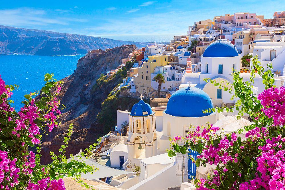 Санторини, Гърция -Емблематичните варосани сгради, които се придържат към скалите с изглед към подводна калдера, манастири със сини куполи и уникално красиви залези. Този егейски остров с формата на полумесец е романтично злато.