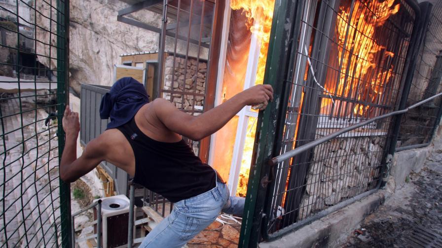 Палестинец до горяща къща на еврейски заселници в Източен Ерусалим