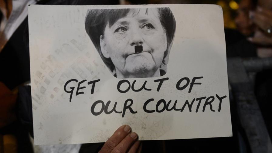 Протестиращ пред парламента в Никозия показва плакат с лицето на Ангела Меркел с нарисувани мустаци, които да я оприличат на Хитлер