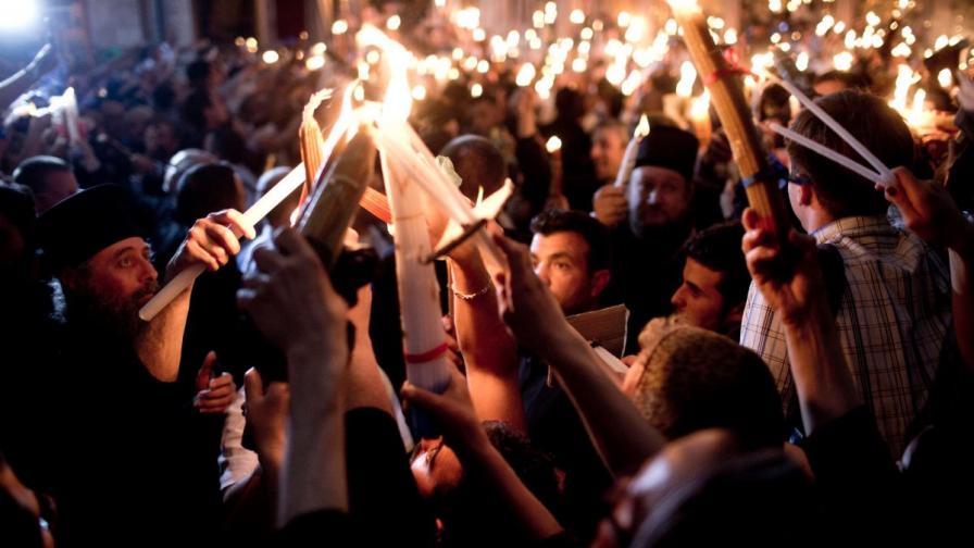 """Православни християни палят свещите си от Свещения огън в църквата """"Възкресение Христово"""" в Стария град на Йерусалим"""