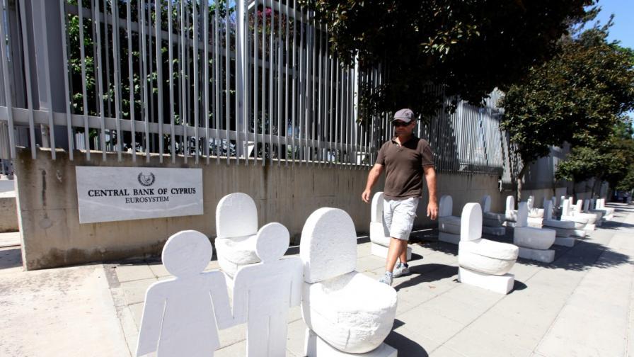 Тоалетни и надгробни плочи пред входа на централната банка на Кипър